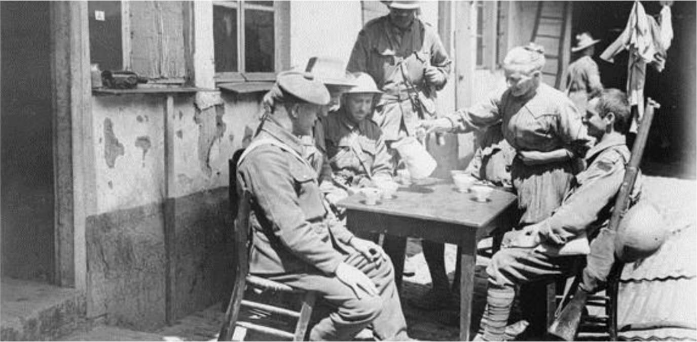 WW1 photograph of soldiers sat at a table socialising outside a cafe in army uniform