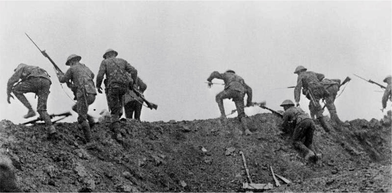 Black and white photograph of troops going over the top of a trench into battle
