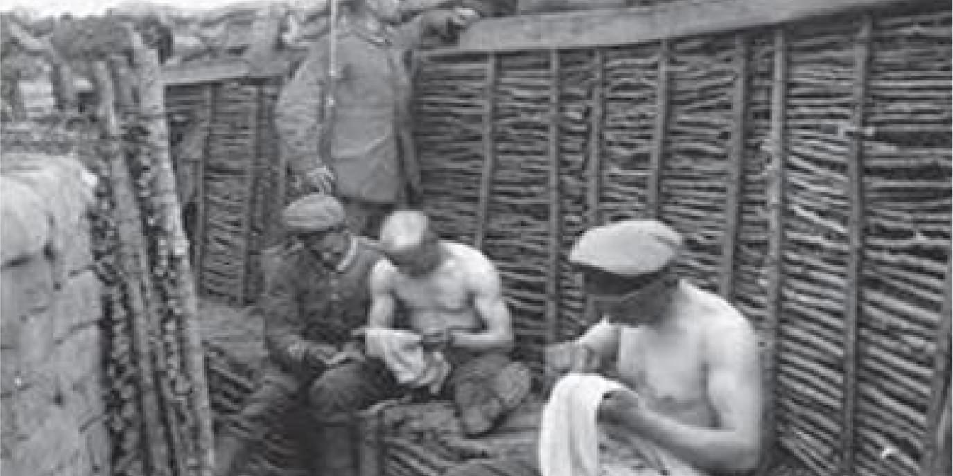 Bare chested soldiers tending to their clothes in a trench in the First World War