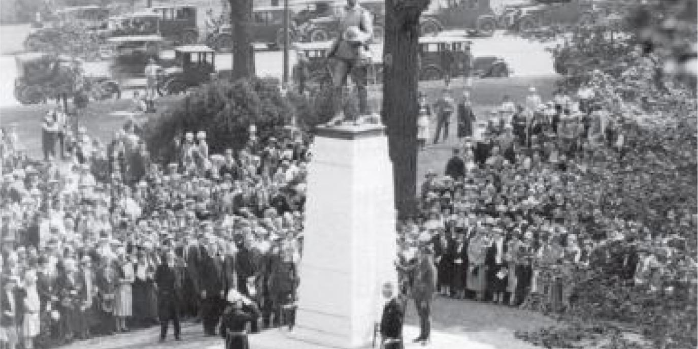 Soldiers gathered to pay tribute at a war memorial, circa 1918.