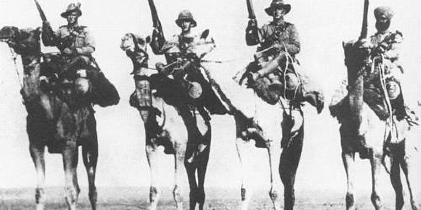 Canadian troops with rifles photographed on camels