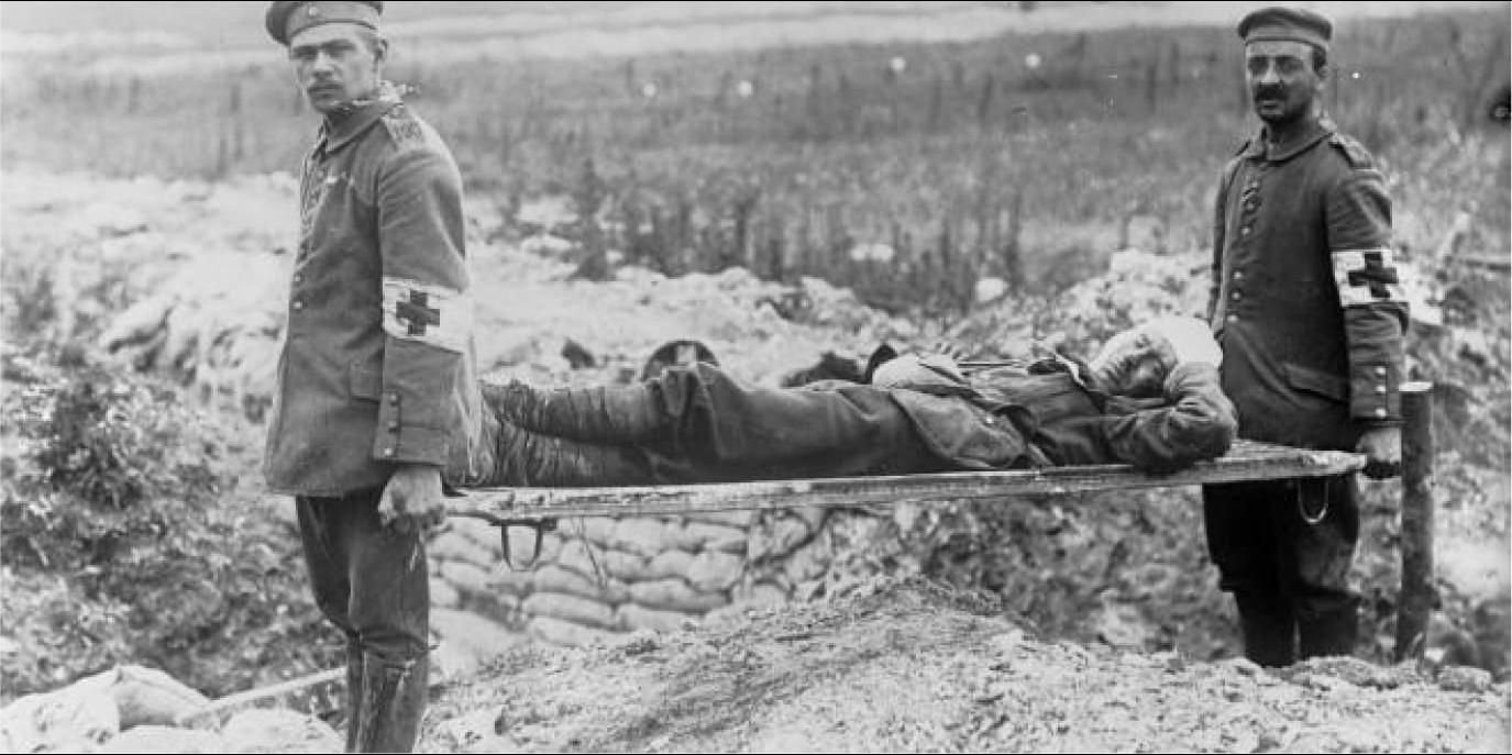 Two stretcher bearers carrying an injured soldier away from the battlefield in World War 1